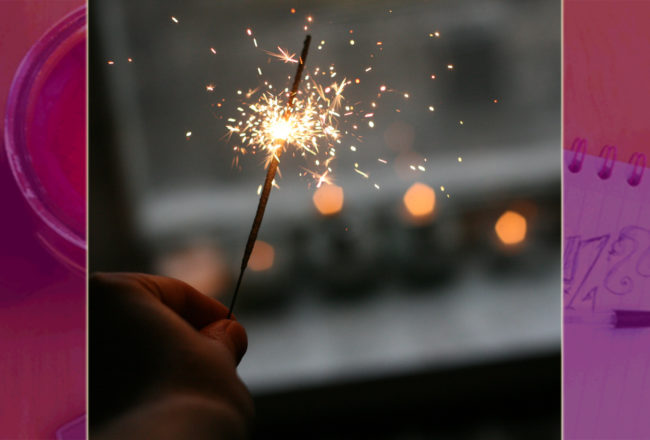 hand holding a sparkler at a window